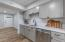 Gray shaker cabinets, subway tile backsplash and quartz countertops complete the kitchen!