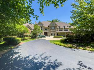 Spectacular 13,000 sq. ft ''Mini Estate'' w 3 levels of uncompromising craftsmanship, Architecturally Designed w/ Normandy influence, Custom Built with accents of Stone/Brick. Open floor plan with magnificent views from every window overlooking the 1.5 acres of woodlands, glistening hardwood floors, beautiful white wood trim, 5 fireplaces, dynamic Great Room w covered Deck, Gourmet Kitchen with spacious Hearth Room, 1st FL Owner's Suite w separate sitting area with FP and Balcony, Walk-Out LL, w enormous Rec Room with Bar/Kitchen, 12 seating Theatre Room, Game Room, sensational Wine-Cellar, full Exercise room, huge enclosed 4 Seasons room w 6th fireplace, steps out to (2) stone Terraces. 7 zone HVAC system. Beautiful decor perfect for entertaining w 5 car-garage &carriage house. FABULOUS!