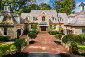 EUROPEAN ELEGANCE and charm in this stately stone & brick Country French Estate. The home is masterfully sited on nearly 3 acres with woods, stream, deep ravine and tended landscaped gardens. Inside are 9,934 sq ft of superior design options of the highest quality construction. Paul Craver Housewright luxury builder paid close attention to detailed crown moldings, coffered ceilings, wainscoting, art niches, bookcases, Brazilian cherry floors, 1st floor Owner's Suite + bath w/heated marble floors, 7 fireplaces, 2 & half story Great room, 13' ceiling height in walkout lower level complete with Kitchen & Bar, Billiards Room, 12 seat Theatre Room, indoor counter-current swim pool and Potting Shed Out Building. A wood shake roof, stone bridge & brick courtyard complete this exceptional home.