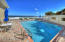 Beach house pool with lounge chairs, tables/chairs/umbrellas, and BBQ grill.