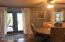 Dining room with arched entry ways, wood floors, French doors leading to the lanai and pool.