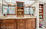 Storage galore in the master bath with wooden built out linen closet and designer medicine cabinets.