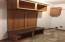 Built in bench storage and cabinet and hanging area by the washer/dryer space