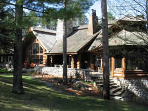 Log home with custom sculpted railings, giant rock fireplaces, gourmet Kitchen with fossilized river rock back splash, large home theatre, 3 Kitchens, wine cellar, indoor pool, spa with waterfall, golf simulator, incredible master suite and more!