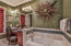 Spa like bathroom with jetted tub, walk in shower, and dressing area.