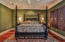 King bedroom with hardwood floors, sitting are, walk in closet and private bathroom.