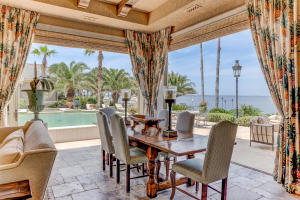 Al Fresco dining is yours from the unbelievable All Seasons Outdoor Living Space complete with media area, elegant furnishings, and stunning outdoor chef's grilling kitchen. Note the Peruvian Travertine Flooring, Custom dramatic limestone crowns and casings, and the view overlooking the bay and dazzling zero entry pool and tanning deck.