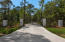 A gated entry leads to a long driveway lined with live oaks.
