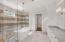 Beautiful master bathroom with walk in shower, tub, herringbone flooring, and quartz countertops
