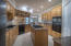 well designed kitchen w/granite counters, island w/gas cooktop, recessed lighting