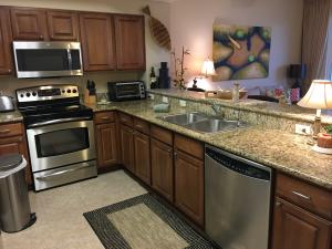 Kitchen offers beautiful granite counters, stainless appliances including a brand new microwave and upgraded wood cabinetry.