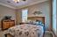 Spacious ground floor guest bedroom with crown molding.