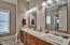 En-suite master bathroom features a large dual sink vanity, dark wood cabinets and elegant tile flooring.
