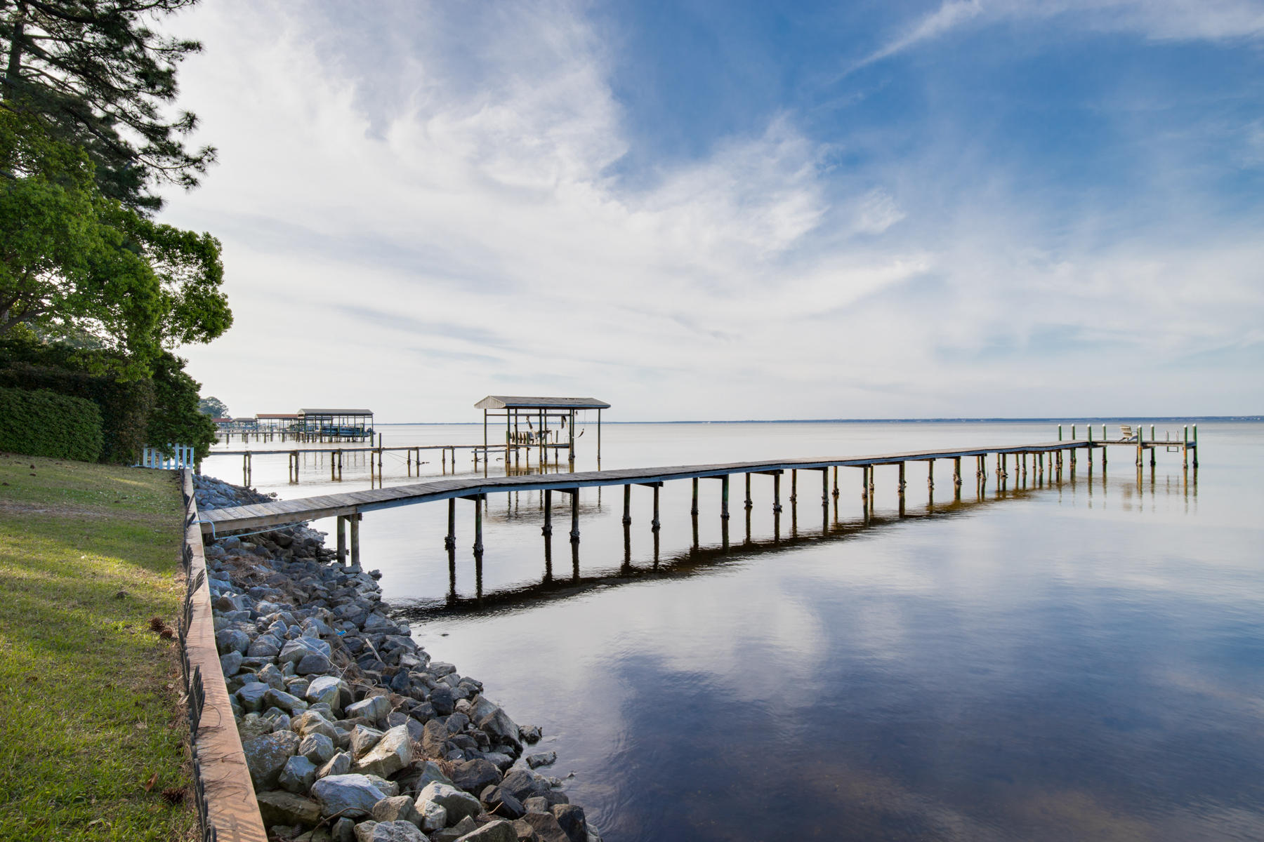 Drastically Reduced! This house is a must see! Graceful elegance, and exquisite Bay views! This custom built Bay front home shows exceptional attention to detail, with phenomenal Choctawhatchee Bay views from almost every room in the house. These views draw you in when you first walk up to the glass front doors! This home is built to last, with premium upgrades and finishes throughout! The spacious, open floor plan is perfect for entertaining. A formal dining room sits adjacent to the large foyer. On the other side of the foyer you are greeted by a large office/library with floor-to-ceiling built-in book shelves that hold over 2,000 books (don't worry, the books are included with the home). The family room features a gas fireplace, and is open to the large kitchen. The kitchen is a dream layout for cooking demos, or hosting dinner parties, with the gas cooktop mounted in the center island and flanked by two spacious pantries and plenty of counter & cabinet space.  The private Master is off the formal living room, and again has excellent bay views. There is also plenty of space with a large wall of built in cabinets, 2 walk in closets, & separate vanities in the bathroom.  On the opposite side of the home there are the 2nd and 3rd bedrooms as well as a hall bathroom, and the large laundry room.  Upstairs you'll find the 4th bedroom and 3rd bathroom as well as a large bonus room that would make an excellent home theater or game room. There are also 2 LARGE attic storerooms, one accessed by a set of stairs in the garage.  Out back there is a large screened in lanai with a hot tub and heated pool with easy access to the dock.  As you walk around the manicured lawn, be sure to check out the putting green tucked away behind the trees. That's right this home has a putting green with a low maintenance artificial turf surface, too help keep your golf skills up in the privacy of your own yard.  House recived a new standing seam metal roof in 2017