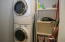 Laundry with full size stackable washer and dryer and custom shelving.