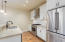 The kitchen includes stainless appliances, granite countertops, and soft-close solid wood cabinetry.