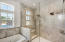 Master bathroom with marble detailing and glass doors