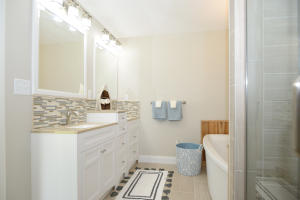DOUBLE VANITY, SOAKING TUB AND SEPARATE SEAMLESS GLASS DOOR TILED SHOWER
