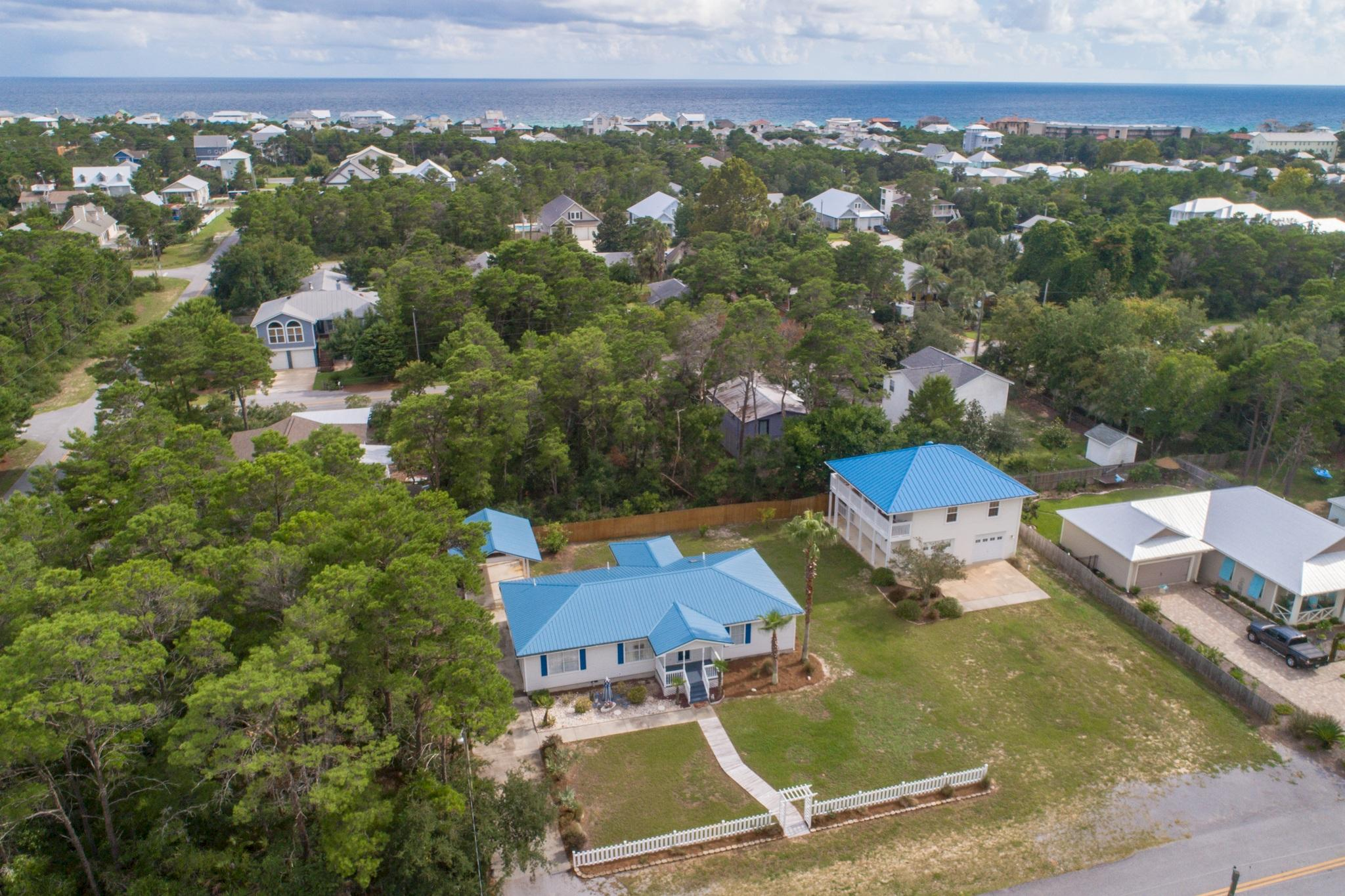 Incredible double lot in the desirable community of Gulfview Heights within half a mile to the beach! This idyllic home has a charming Florida feel, with a 3-bedroom main house and 1-bedroom carriage house over a 2-car garage. There is also room for an additional home in front of the carriage house. It is rare to find a double lot available in the 30A area. This lot totals 0.378 acres. The main house features 3-bedrooms and 2-baths totaling 1,796 sq. ft. and the carriage house is a 1-bedroom, 1-bath totaling 900 feet, however, the 2-car garage also offers an additional full bath and is heated & cooled for a total of 2,184 sq. ft. With welcoming landscaping and a newly painted covered front porch you feel at home. This is a fantastic private oasis for full time living or the perfect rental! Both properties have a new metal roof (2015) for that classic Florida beach cottage feel and the white picket fence welcomes you at the entry. For the main home, the interior features beautiful craftsman details like built-in shelving & cabinetry, stunning Georgia pine wood floors throughout the living area and master bedroom, vaulted ceilings and light cove for a display area. The living area is open to the dining area and a spacious kitchen. The kitchen has ample storage with hardwood cabinets, granite tiled kitchen countertops and breakfast bar for casual dining. Appliances are in great shape and there is a built-in desk for convenience. Access the screened-in back porch off the dining area, which is a great place for outdoor dining and relaxation. There is an added wood ramp walkway for easy access to the back porch from the exterior as well. The backyard view is tranquil and there is an expansive lot where you can expand your entertainment space or even add a pool!   This home is unique for the amount of storage as each bedroom features a walk-in closet and there is a large laundry room with a full size washer & dryer that conveys. The master suite is exceptional with the beautiful pine wood floors, trayed ceiling and view of the front yard. There is an en-suite bathroom with an updated shower featuring natural pebble stone flooring and backsplash. There is also a double vanity and the walk-in closet. There are two spacious guest bedrooms with a shared guest bath with a skylight for great natural light and a shower/tub combo. For this compound there is plenty of parking down the long driveway and also a covered carport and enclosed storage area for all of your beach gear. There is even kayak storage outside to start that outdoor lifestyle.   The carriage home is located above the 2-car garage and was built as an addition in 2004. This space is inviting with an open living area with wood floors, a full kitchen & dining area with tile floors and a spacious master bedroom and full bathroom with double vanity and shower/tub combo. Relax on the covered balcony and take in the tranquil setting & palm trees surrounding you. The 2-car heated & cooled garage is a major plus and an easy spot to create a workshop as there is plenty of space. Store your bikes and beach toys easily and even rinse off that beach sand in the garage bathroom with a walk-in shower. The cost of living is also low here with no HOA fees and each home has its own septic tank. Your monthly public water bill is minimal as the irrigation system is on well water. This is truly a unique property that will not last long!   The location is prime in close vicinity to the beautiful emerald green waters of the Gulf of Mexico and beaches of South Walton, with the Gulfview Height beach access within reach. You are also close to Gulf Place - one of 30A's main entertainment hub's with an outdoor amphitheater offering live music during the summer concert series and great events throughout the year. Stop for your morning coffee at Sunrise Coffee, get your beach gear at the 30A store, rent a paddle board at YOLO Board and grab breakfast or dinner at La Playa and other dining spots. Everything you need is at your fingertips - what a convenience to get here by a quick bike or golf cart ride. The Long Leaf Trail Head is also just a couple of blocks away where you can enjoy nature trails and beautiful pines throughout the state park. This is a main spot for biking and hiking. Your coastal paradise & beach lifestyle awaits!