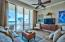 Floor to ceiling glass sliders in the living room provide spectacular views of the gulf and tropical landscaping outside. Tile floor, crown molding, and comfortable decor create a classic beach lifestyle atmosphere.