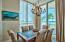 The dining area is awash in fresh natural light from the large window and floor to ceiling slider. Crown molding, plantation shutters and beachy shabby chic decor lend a sophisticated feel to this warm and casual space.