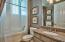 This bathroom features a tile shower, plantation shutters and a granite vanity.
