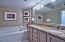 This master bath features a his and hers vanity, tray ceiling, tiled walk-in shower, and a separate whirlpool tub.