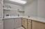 The laundry room includes full size washer and dryer, shelves, cabinet space, and a utility sink.