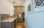 Galley kitchen boasts custom tile backsplash, granite counter tops and soft close cabinets