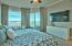 The harbor front master bedroom is furnished with a king bed, large flat screen TV, and breathtaking views.