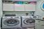 Laundry room with full size washer and dryer and additional storage.
