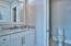 The en-suite bath features marble vanity, pocket door, and walk-in tile shower.