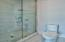 Glass and tile walk-in shower with rainfall shower head.