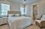 Plenty of natural light, shiplap walls, custom molding, en-suite bath with pocket door and the beautiful Ash wood floors combine to make this a welcoming bedroom.