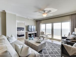 Gorgeous sophisticated neutral living area features sliding glass doors giving off lots of natural light from the beachfront views!