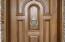 Close-up of 8' tall custom designed mahogany front door with Baltic custom made solid satin nickel door knocker from Hungary.
