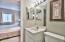 Convenient en-suite half bath from the master with vanity and tile floors.
