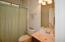 Bathroom has Sliding Glass Shower Door behind curtain.