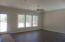 Family Room has tall windows with lots of natural light. Tall 8' door leads to Lanai.