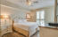 Spacious king size master bedroom with access to balcony and wall mounted tv