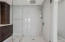 Large, glass-enclosed shower with multiple shower heads.