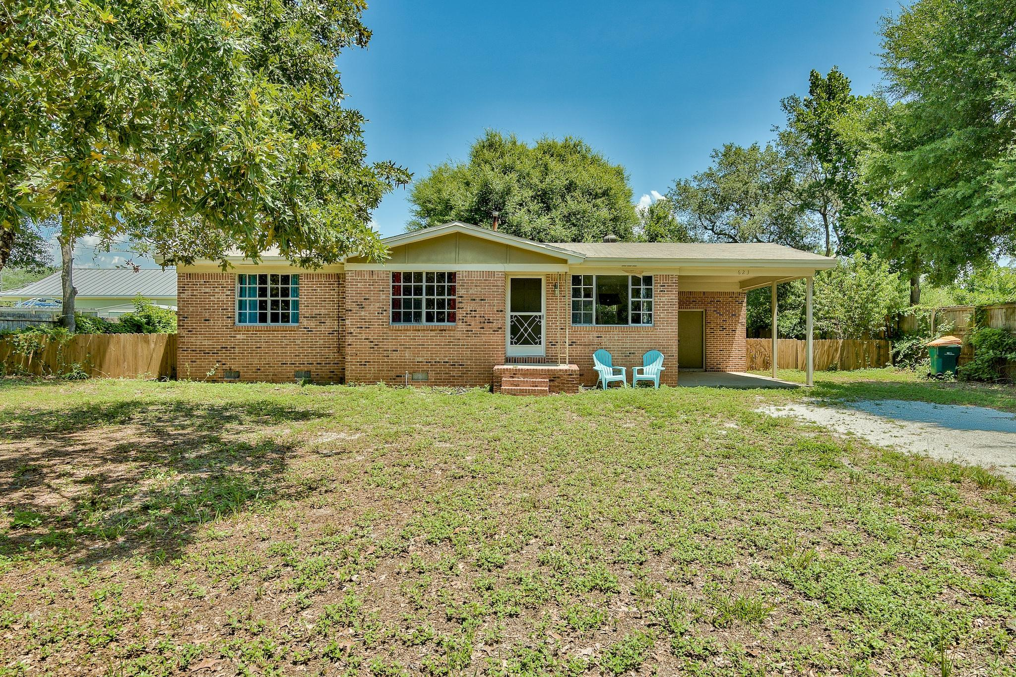 A deal this good in the Destin area will not last long! Charming 3-bedroom brick house with an attached single car carport located on a large lot in the heart of Destin. No HOA! Perfectly located near premier shopping, dining and beautiful white sand beaches. The house is only one block from the Destin Elementary School and just minutes from Destin Harbor. The renovated kitchen has a new tile floor, granite counters, added backsplash, new cabinets and new Whirlpool appliances. The bathroom features a granite shower & counter as well as a new tile floor. The home boasts real hardwood floors throughout. Enjoy the fenced backyard & front yard has beautiful trees and plenty of space for additional parking. You could even park a boat & trailer and have Joe's Bayou boat launch nearby. This home has an incredible fenced-in backyard large enough to add a patio/deck, shed, pool or even plant your own garden. The large backyard is a great place for the children and pets to run around and play! This home has a lot to offer and would make a perfect first-time home or rental property.