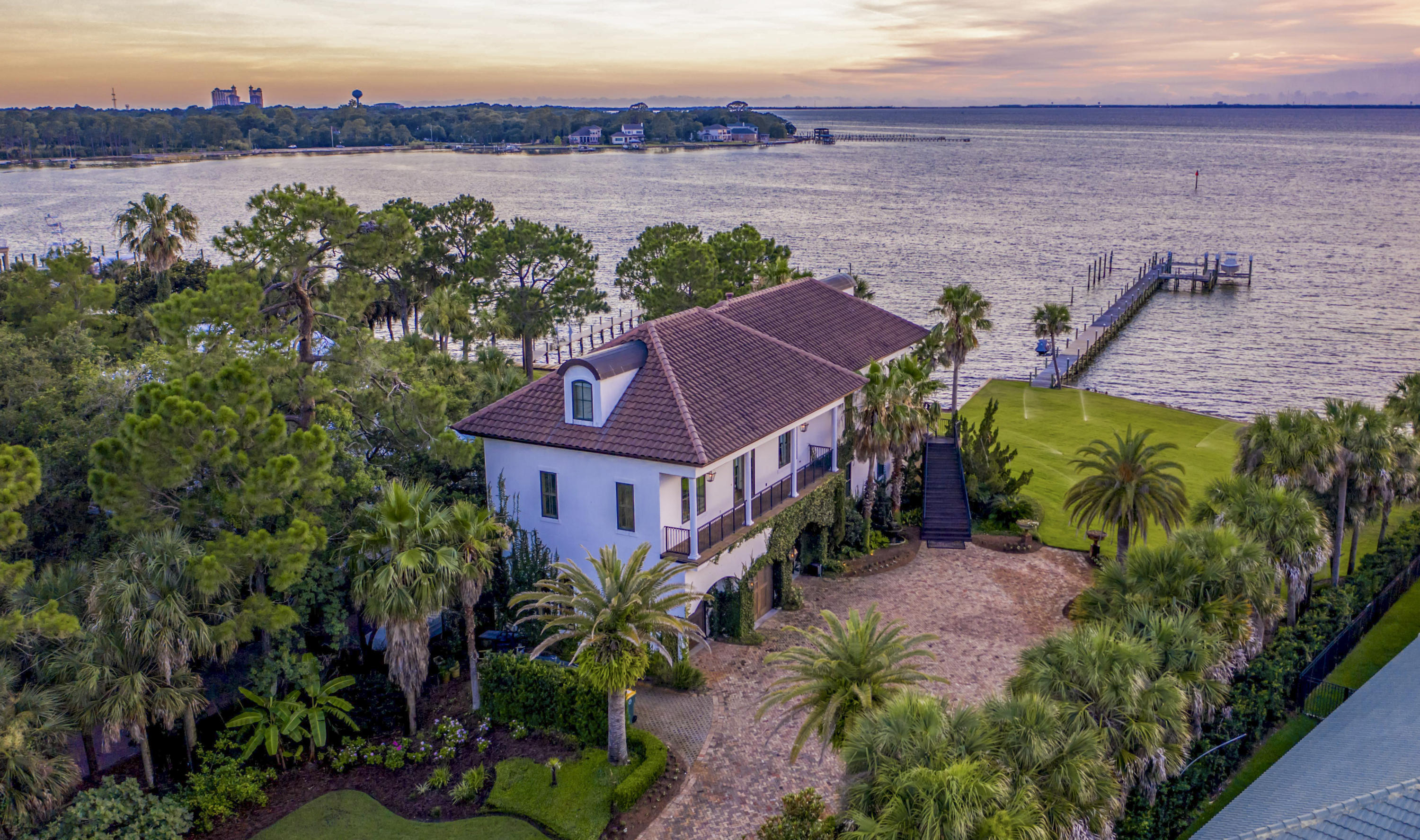 One of the finest lots in Destin, Florida, located in the exclusive Cobb's Point! Measuring nearly one acre, with approximately 180' of water frontage at the coveted point of Joe's Bayou and Choctawhatchee Bay, the property features the most desired west-facing orientation, providing stunning sunset views, afternoon light, and a phenomenal dock that will accommodate large boats! Evoking the classic beauty of old-world France, the home is built with generations in mind. It features many imported finishes, as well as superior ICF construction and modern technologies designed for longevity in the north Florida climate. The flexibility of the 3-story floorplan promotes the interests of generations as well: the main living space and master suite are on the second floor, with 2 additional... bedroom suites plus a connecting living area on the third level, and a first floor apartment with another gorgeous master suite, which can either be self-sufficient, or easily reached via connecting stairs or the elevator.          Gorgeous Bois Chamois French white oak floors, shipped from France, comprise the wide-plank floors on the first two floors. In addition to stunning water views, the open entertaining area includes a tea bead chandelier from India setting off the dining area and a coral stone fireplace with surround sound incorporated. Truly one of a kind, the kitchen features Bevolo gas lanterns, old Chicago brick accent wall, a LaCornue range from France with full concrete hood, French Herbeau faucets, custom-painted cabinets, poured concrete countertops, and an amazing island custom built over an antique church altar. Custom woodworking was employed in the adjoining pantry. Nearby are an office, with dual computer desks and hand-carved, antique doors, and a powder room for guests boasting a giant clam shell sink and antique Belgian mirror.                       It may look elegant on the outside, but this is a full-fledged dream garage! Over 1300' of conditioned space and
