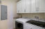Large laundry room, complete with new washer and dryer, custom cabinets, basin sink and granite surround