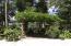 This pergola has lighting and lush vegetation all around it.