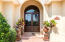 Reminiscent of Old World architecture | mahogany doors w glass panes & bronze scrollwork