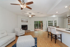 Large family room with wood laminate floors, double ceiling fans, built in speakers, and fireplace (gas or wood).