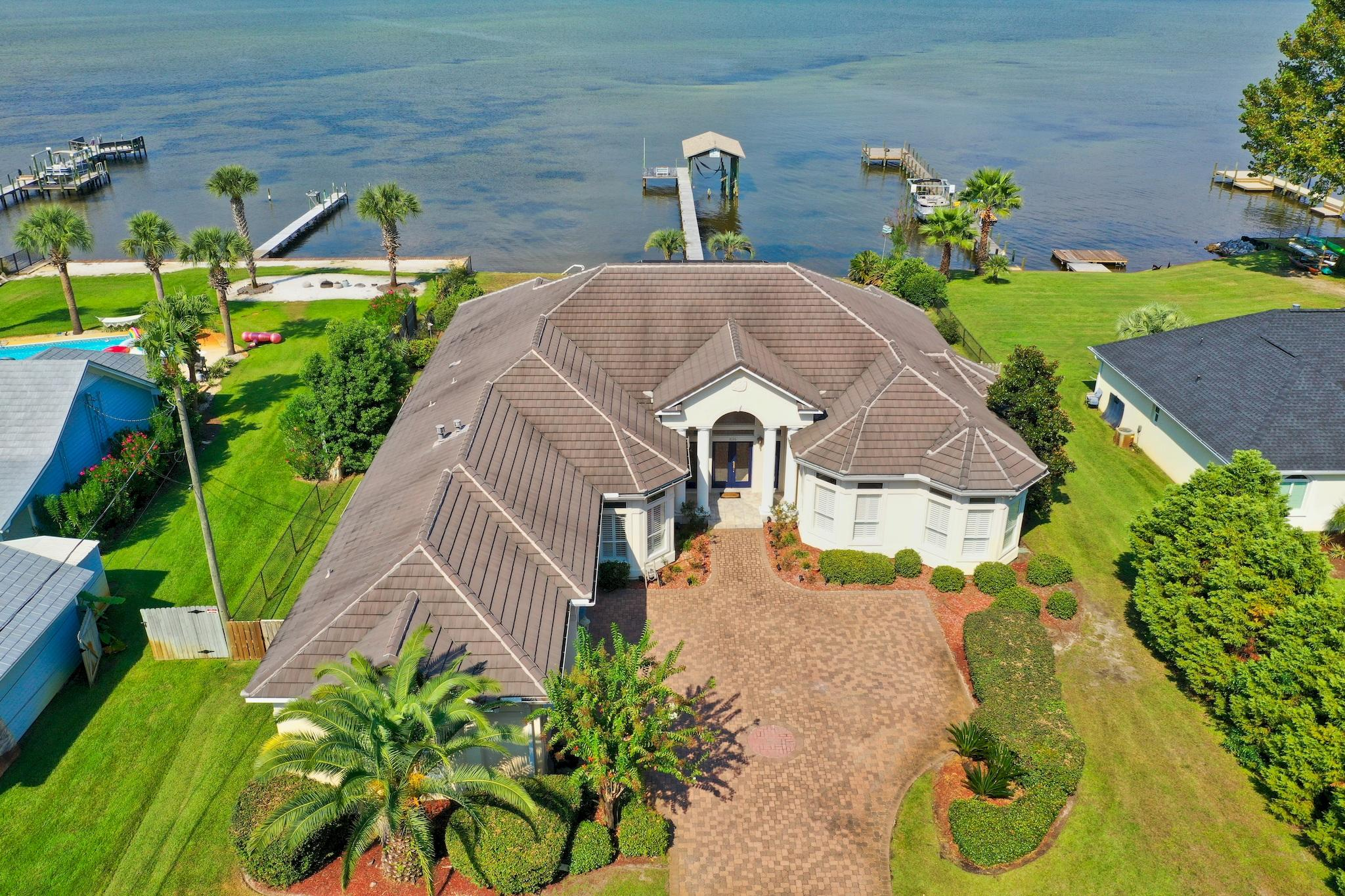 Enjoy coastal living in a serene tropical setting with this Bay front estate in Miramar Beach! This home is on an expansive and private lot boasting over 1/2 an acre.  With 100 ft of water frontage on the Bay, you have your own private oasis! Home is complete with dock, boathouse with slip, sun deck, incredible screened-in pool and covered lanai. Outdoor features a huge back yard with tropical landscaping setting this home apart from the rest. *Check out the lifestyle video and virtual tour of this amazing property in the Photos section.* Ideally the home is one level with beautiful architectural details like trayed ceilings, stunning archways, crown molding & lots of windows offering great natural light and panoramic views of the Bay. The interior has been repainted for a fresh look along with new chandeliers, new hardwood flooring and updated kitchen & baths with Quartz countertops. Kitchen also includes new stainless steel appliances including a double oven and smooth top range, new custom tiled mosaic backsplash, and freshly painted kitchen cabinets. There is a wet bar nearby with a wine fridge, sink and extra storage as well as a generously sized walk-in pantry. The full bath for guests is stunning with newly tiled shower with glass door and Quartz counters. There is also a half bath near the kitchen which is easy access while entertaining. There are 4 bedrooms including a Bay front master, an additional flex room and 3-car garage. The beautiful master bedroom features a tray ceiling, several windows allowing views of the Bay from just about every angle, wood flooring, a master closet with built-ins and an en-suite bathroom. You will feel like you are at the spa in the master bath with Jacuzzi tub, double vanities newly appointed with Quartz and walk-in tiled shower with glass block entrance and recessed lighting. The split bedroom floor plan allows the master bedroom extra privacy away from the other three guest bedrooms. All three guest bedrooms are generous in size and feature crown molding and plantation shutters. There is a great flex room located at the front of the home east of the foyer that would make a terrific office.   The large, covered lanai is the perfect spot to relax and can be accessed from several rooms in the house including living area, dining nook, great room and master bedroom. The screened-in pool area with paver sun deck is ideal for tanning then cooling off with a refreshing swim. The covered porch was freshly painted and offers a fantastic swing to lounge in while taking in breathtaking views of the Bay. Incredible opportunity to own such a prime location with over half an acre of direct Bay front, and just 5 minutes from the pristine beaches along the emerald green waters of the Gulf of Mexico! You can easily access the beach by golf cart across Holiday Road and are also near many dining, shopping and entertainment options. This is an amazing opportunity for coastal living!  *****Appraisal at $1,200,000 from last year when they refinanced. Available upon request.