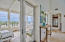 Expansive glass doors opening to covered porch overlooking the Seaside grassy park and shops
