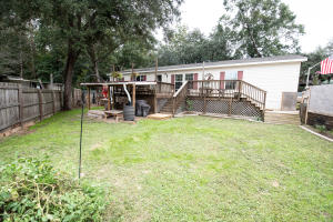 Front view with large deck, covered swing, grill area, and rain barrell for your watering.